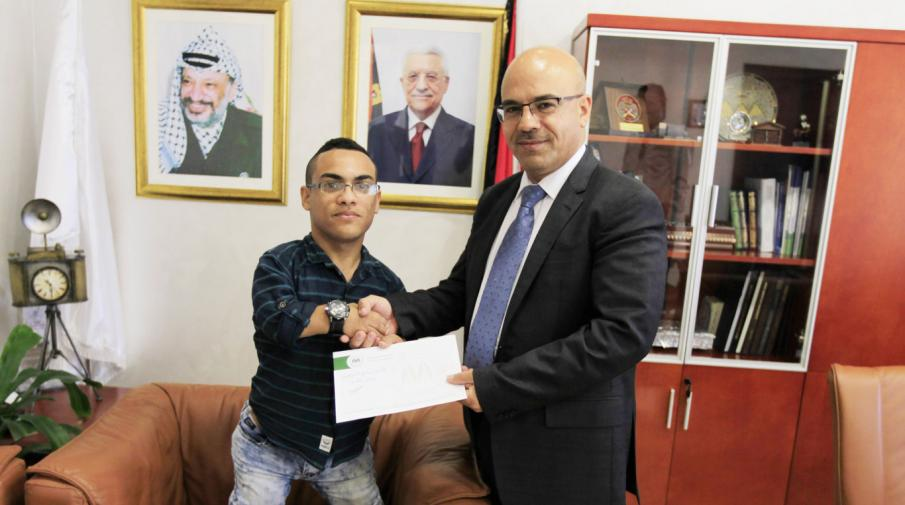 University President Assistant for Administrative and Financial Affairs Mr. Faleh Abu Arra delivered the scholarship decision to the student in representing Chairman of Directors Board.